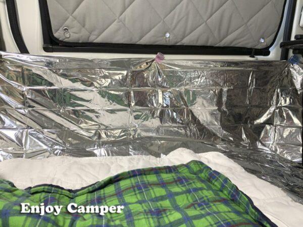 窓には遮光パネル、ベッド上には銀シート、敷きパッド、寝袋を重ねて防寒対策